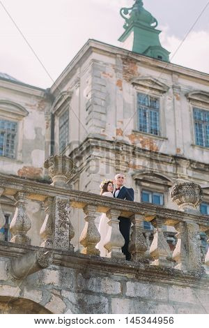 Charming newlywed bride and groom kissing near beautiful ruined baroque palace.