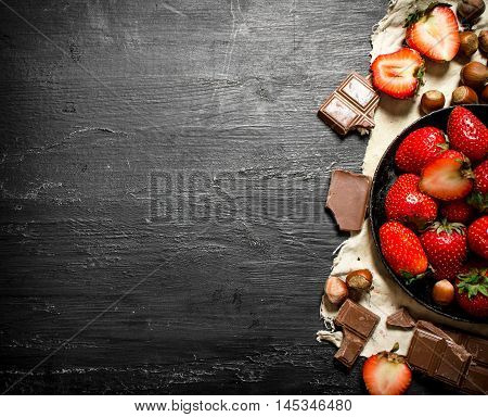 Strawberries with slices of chocolate and nuts. On the black wooden table.