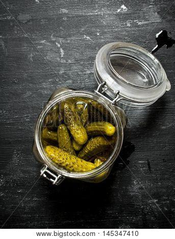 Pickled gherkins in a jar. On a black wooden background.