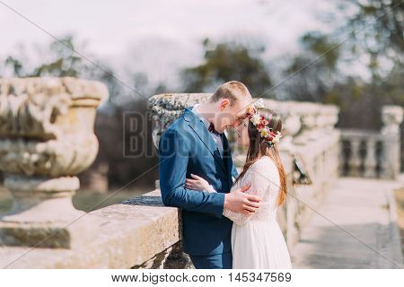Wedding portrait of stylish newlywed couple posing at old stone terrace in spring park and lovingly touching by foreheads.