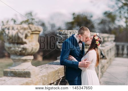 Wedding portrait of stylish newlywed couple passionately kissing at old stone terrace in spring park.