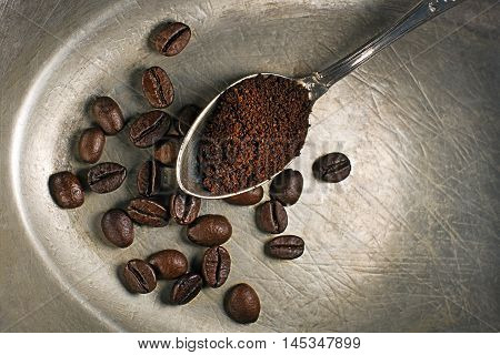 Fresh ground Coffee in spoon on wooden background.