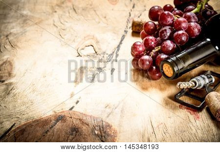 Bottle of red wine with a sprig of grapes and a corkscrew. On wooden background.