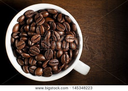 Fresh coffee beans in cup on wooden background