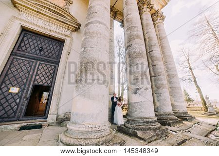 Young wedding couple posing near antique building columns with leafless park trees at background.