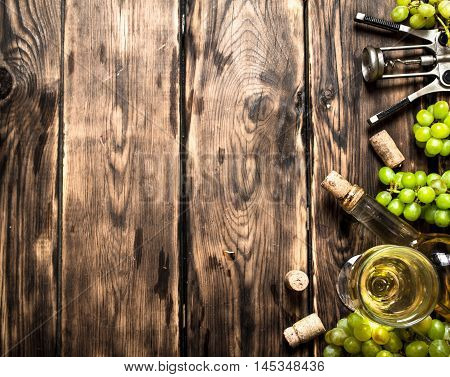 White wine with a corkscrew and branches of grapes. On a wooden table.