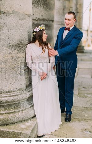 Young wedding couple posing outside near atique building with columns.