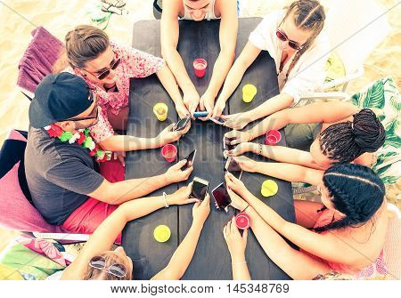 Best friends group holding mobile phone top view at beach cafe bar restaurant - Many teenagers having fun in a circle around wooden table with beverage scene from above - Technology addiction concept