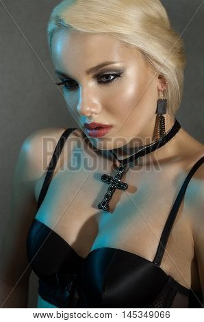 girl the blonde with a cross on a neck in black brassiere in studio