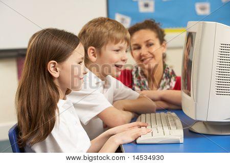 Schoolchildren In IT Class Using Computer with teacher