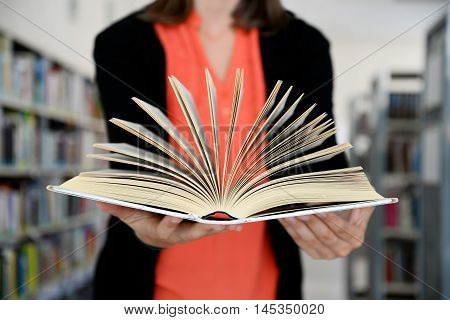 Close up of opened book in woman's hands.