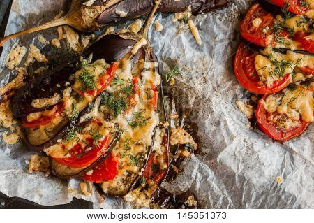 Baked eggplant in a fan shape on a baking sheet top view. Cooked with tomatoes and cheese. Sauce - olive oil garlic dried oregano and basil sprinkled with fresh dill.