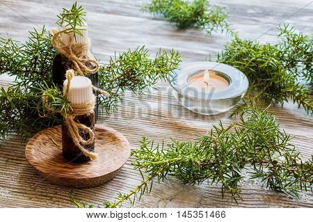 Juniper essential oil in a glass bottle on a wooden table. Used in medicine cosmetics and aromatherapy. Fresh green sprigs and burning candle. Selective focus.
