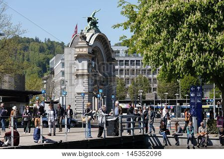 LUCERNE SWITZERLAND - MAY 05 2016: Unidentified passers around massive arch that is all that remains of old railway station burned in 1971
