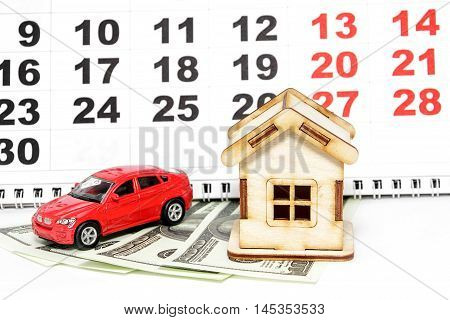 Wooden house red car and the dollars on a calendar background