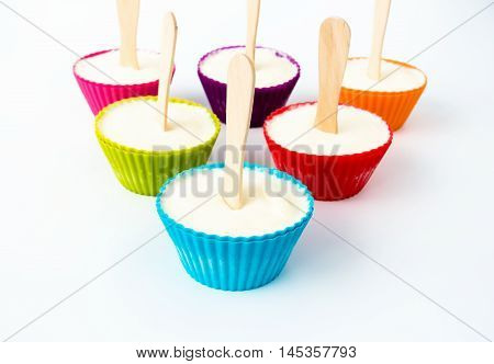 Six colorful cupcake cases with a wooden ice lolly stick in the middle filled with vanilla ice cream and arranged in a triangle.