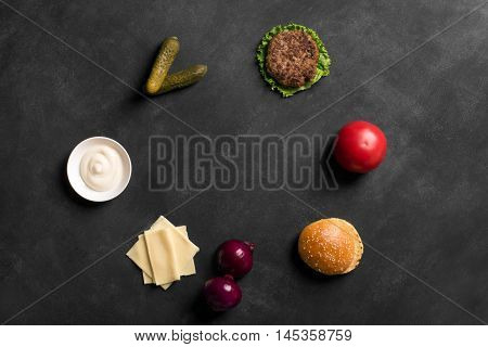 Beef burger with lettuce and sauce on the black chalkboard. Ingredients of popular takeaway food with copy space