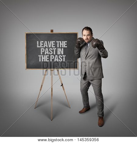 Leave the past in the past text on  blackboard with businessman wearing boxing gloves