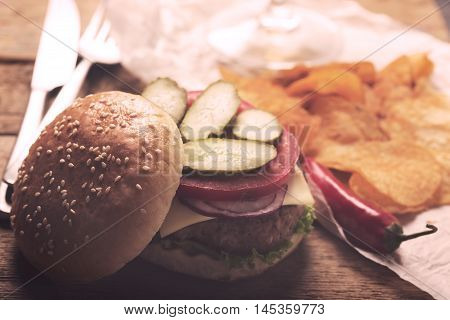 Beef burger with lettuce and minced meat cutlet. Potato chips and glass of beer. Retro style