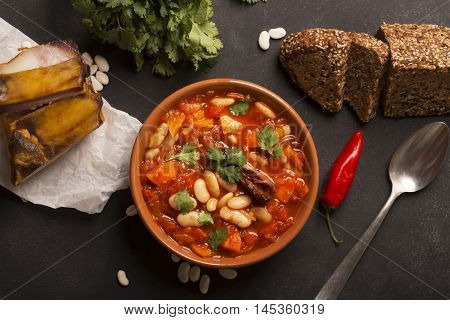 Rustic Kidney Bean Soup with beans and carrot. On the black chalkboard. Top view
