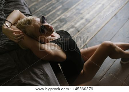 woman with bare feet in black sneakers and body sits near a large bed on the wooden floor, looking at the camera and posing for a photograph with his hands near the face. woman posing beside the bed and holding his hands behind his head