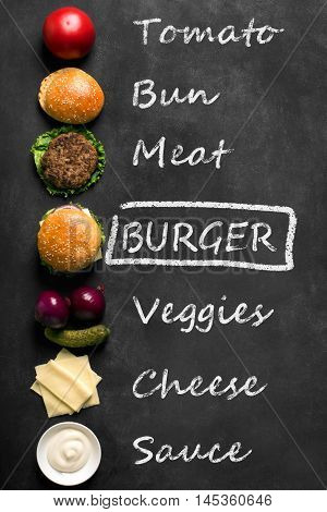 Beef burger with lettuce and minced meat cutlet. Black chalkboard. Top view