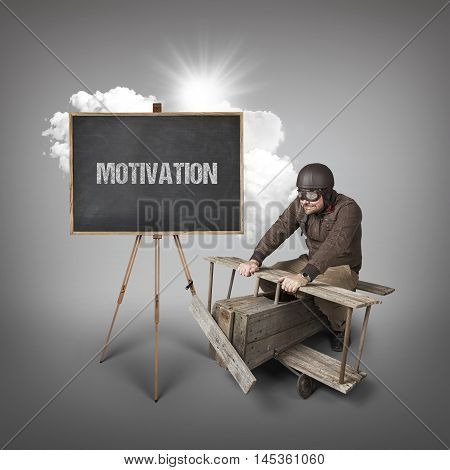 Motivation text on blackboard with businessman and wooden aeroplane