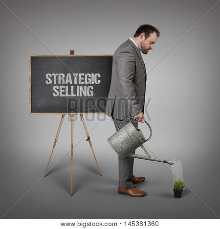 Strategic selling text on  blackboard with businessman watering plant