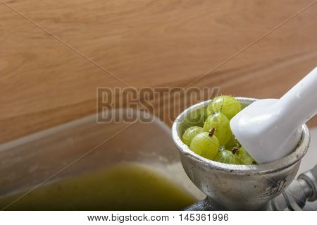 green gooseberries are squeezed in a juicer - Close-up