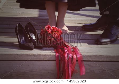 Close up of bride's and groom's feet and wedding bouquet of flowers