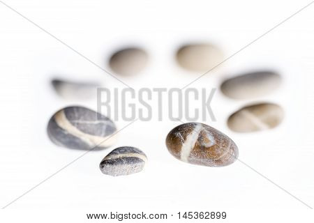 macro shot of a circular arrangement with small pebbles in white back