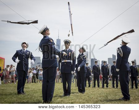 JERSEY CITY NJ MAY 29 2016: The US Coast Guard Ceremonial Honor Guard Silent Drill Team perform air-toss movements with fixed bayonets on rifles in Liberty State Park during Fleet Week NY.