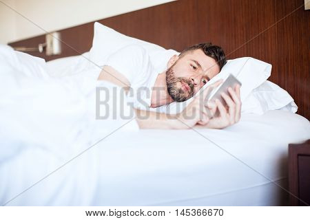 Young Man Texting In Bed