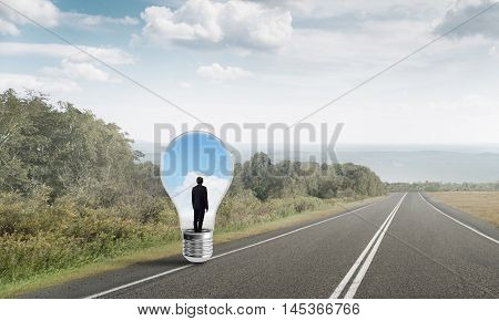 Young businessman trapped inside of light bulb on asphalt road