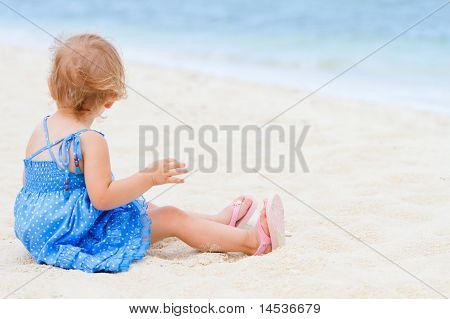 Toddler Girl Sitting On White Sand Beach