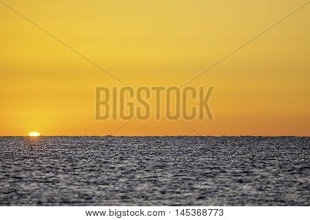 The sun emerges on a new day over a clam sea. Symbolises eternal hope on a beautiful planet. Soft foreground with plain background suitable as copy space or for montage.