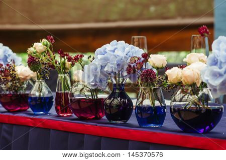 Beautiful decor at the wedding. Flowers standing on the table.