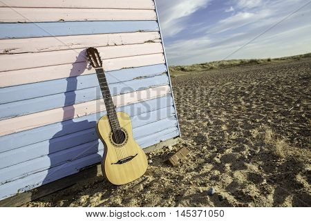Parlour-sized classical acoustic guitar resting against a beach hut painted in pastel pink and blue. Symbolic of vacation and beach fun. Exaggerated angle shows the guitar; beach hut; sand and blue sky