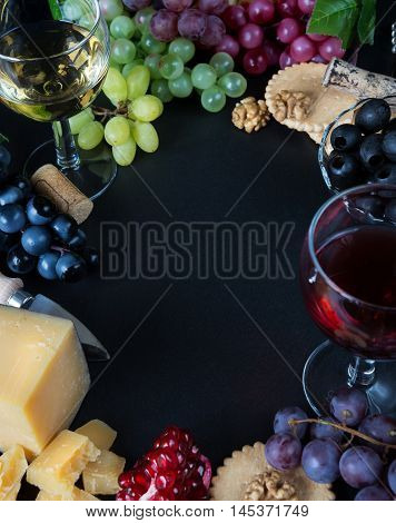 Wine and snacks arranged in the form of a border on a black background