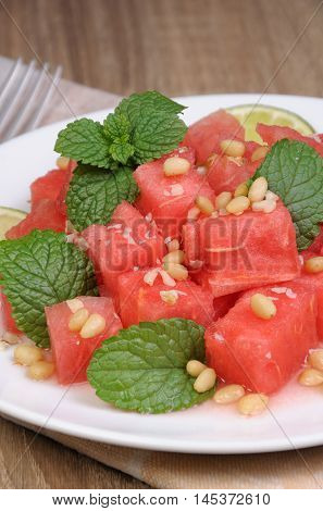 A refreshing salad of watermelon cubes with slices of lime mint peanuts pine nuts