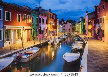 Colourfully painted houses facade on Burano island in evening, province of Venice, Italy
