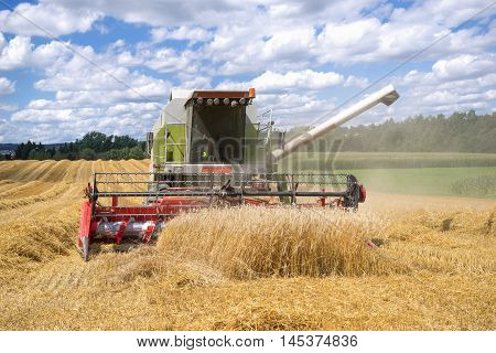 Working combine harvester from the front when harvesting a grain field