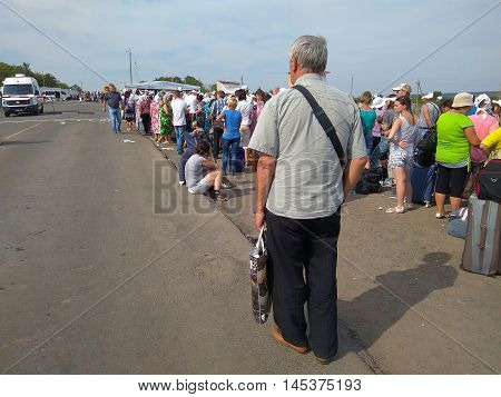 Zaitseva, Ukraine - August 22, 2016: People stand in line at the intersection of the checkpoint in the area of anti-terrorist operation