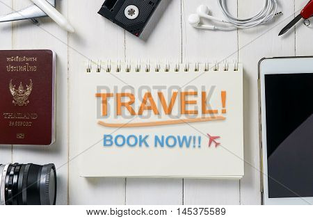 Travel Agency booking Banner with text Travel Book Now on book page. Travel equipment surrounding the Ring Binder with Travel book now message.