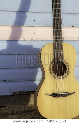 Parlour-sized classical acoustic guitar resting against a beach hut painted in pastel pink and blue. Symbolic of vacation and beach relaxation.