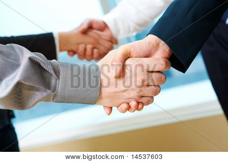 Photo of two pairs of partners arms handshaking after striking deal