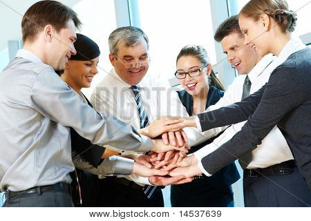 Photo of smiling co-workers making pile of hands and looking at camera