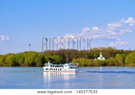 VELIKY NOVGOROD RUSSIA -MAY 3 2016. Summer architecture landscape - church of John the Evangelist on the Vitka and sailboat floating the Volkhov river in summer evening in Veliky Novgorod Russia