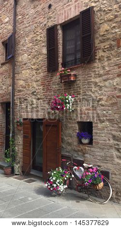 Bicycle and flowers in front of a home in the medieval city of Castiglione del Lago, Umbria, central Italy
