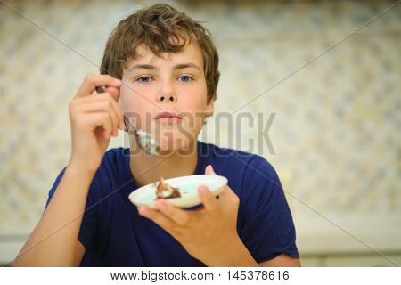 Happy boy teen eats confection from saucer in kitchen, shallow dof